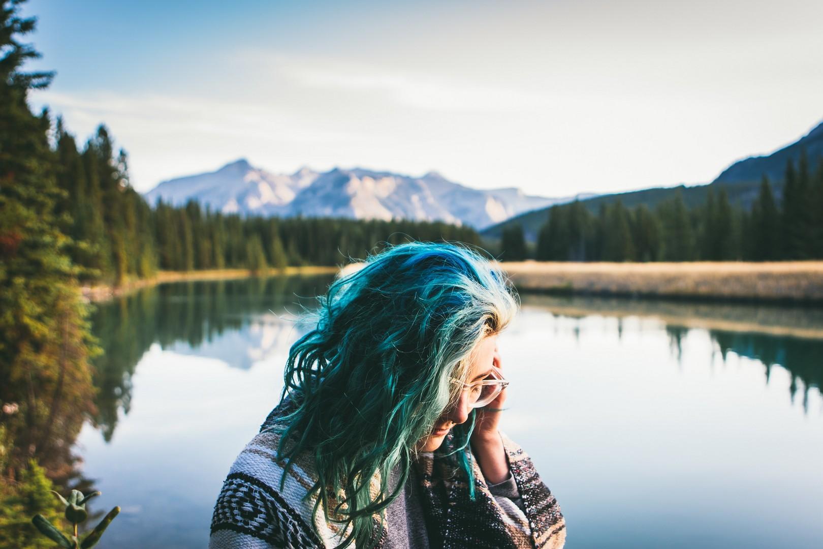 Mulher olhando para baixo, de perfil, cabelos azuis com mesclas loiras, em uma paisagem repleta de coníferas, com um lago atrás e montanhas ao fundo.