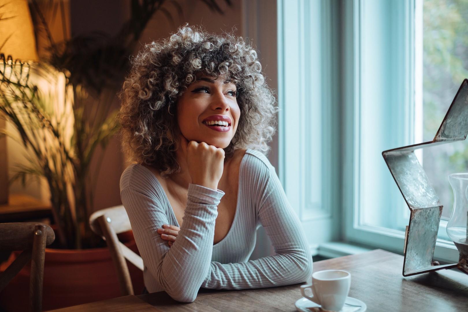 mulher de cabelo cacheado, curto e loiro, tomando café enquanto sorri
