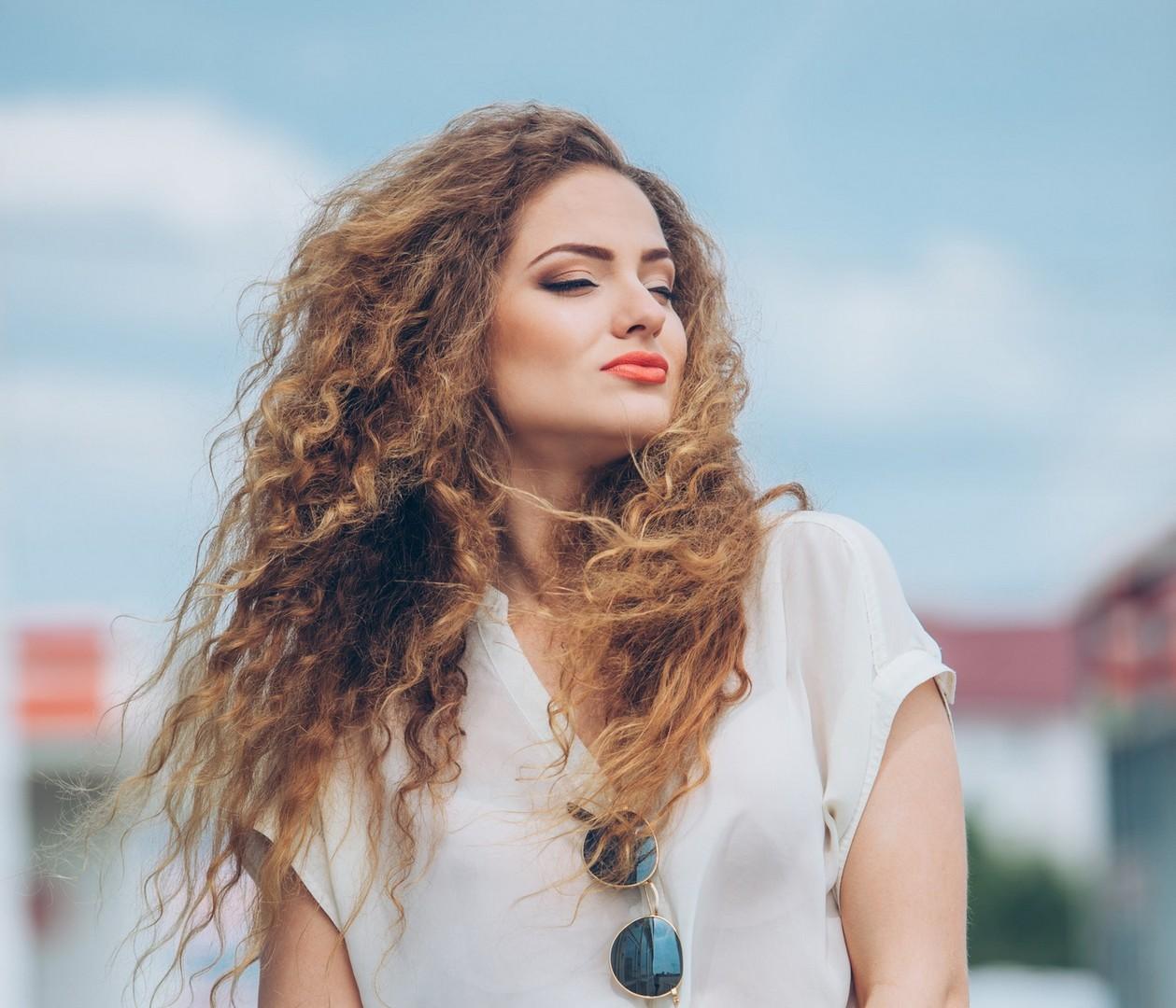 mulher de cabelo castanho claro cacheado