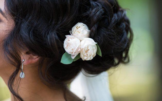 Coque com arranjo de flor em cabelo ondulado curto