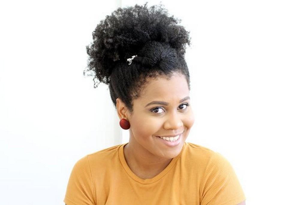 Mulher de cabelo cacheado, curto, preso em um afro puff