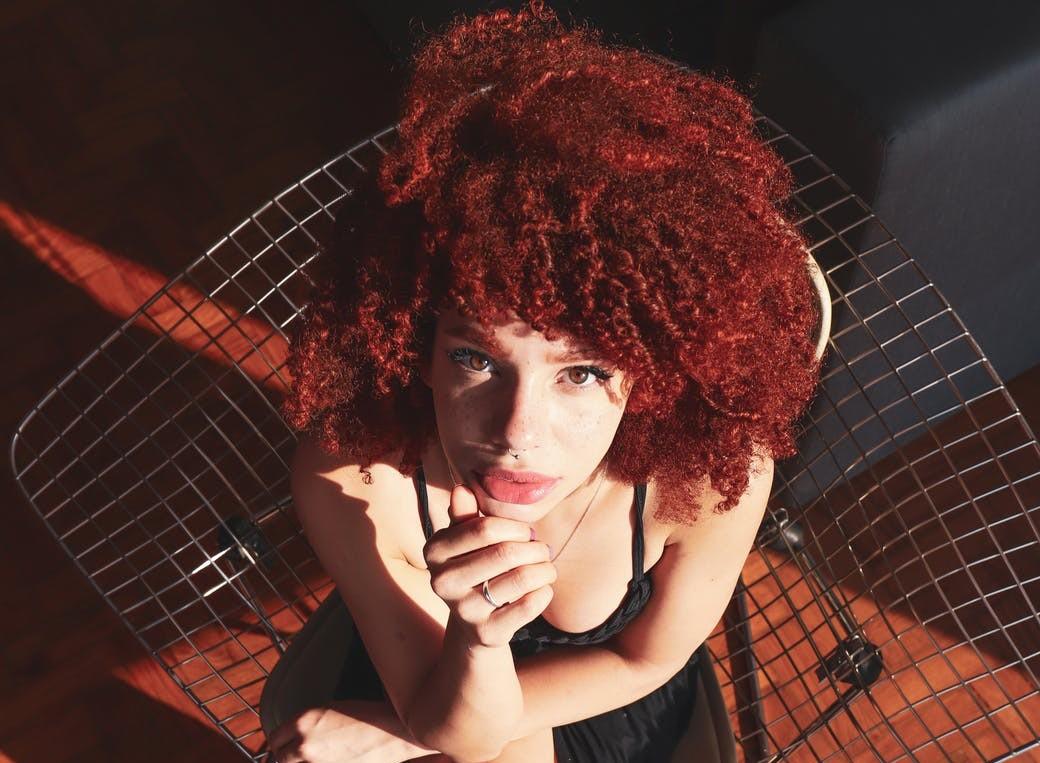 A modelo sai na foto com o seu cabelo cacheado com volume avermelhado para mostrar toda sua beleza na foto